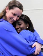 Jochebed Oduro is hugged by classmate Jessica Touchstone after Abilene Christian High School graduation ceremony. The two were teammates on the school's volleyball team.