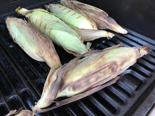 Fresh corn cooked in the husks on the grill.