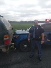 Michigan State Police Trooper Timothy Roberts of the Marshall post with the damaged vehicles.