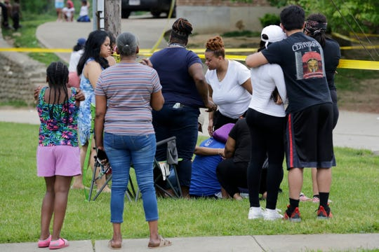 Neighbors and family members gather outside the caution tape as police investigate at the scene of a shooting on the 5800 block of Hawaiian Terrace in the Mt. Airy neighborhood of Cincinnati on  Sunday, May 17, 2020. The homicide unit was called to investigate the scene where an 8-year-old boy was shot and killed Sunday afternoon. The incident is still under investigation.