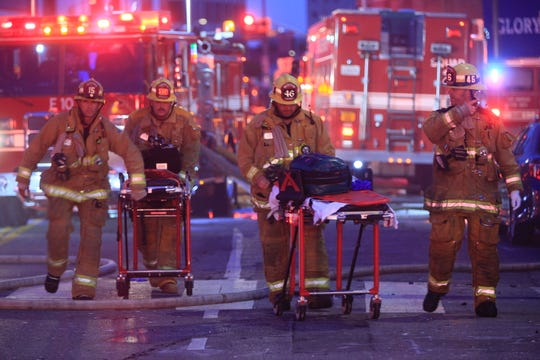 Los Angeles firefighters push ambulance cots at the scene of a structure fire that injured multiple firefighters, Saturday, May 16, 2020.