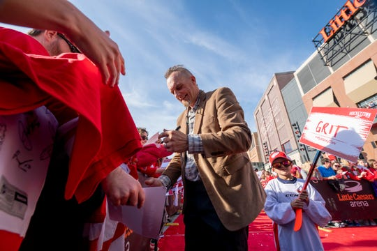 Darren McCarty signs autographs during a red carpet entrance before the Red Wings' home opener in 2019.