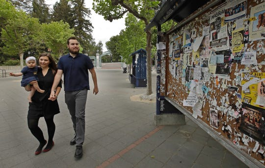 University of California at Berkeley graduate Tyler Lyson walks with his wife, Lucie, who is holding their daughter, Lisa, as they walk past a student activity billboard on the closed Cal campus in Berkeley, Calif., on May 11. The 27-year-old won a full scholarship to the University of California-Berkeley and will become the first in his family to earn a degree.