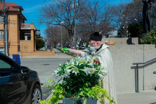 In this April 11 photo, Rev. Timothy Pelc blesses Easter baskets outside St. Ambrose Church in Grosse Pointe Park. Pelc, wearing church vestments and protective gear, offered a prayer and sprayed holy water from a squirt gun instead of blessing baskets inside the church in a bid to maintain social distancing during the coronavirus pandemic.