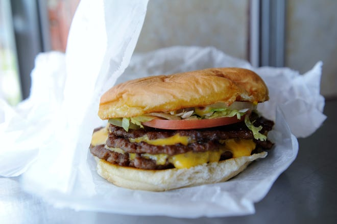 A fully-dressed triple cheeseburger from John Earl's with lettuce, pickle, tomato, onion, mayo, mustard and ketchup.