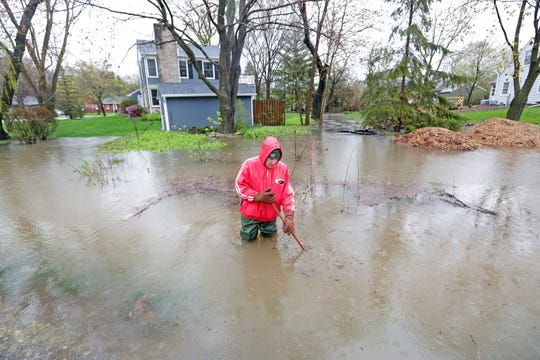 A Bayside resident, who didn't want to give his name, removes debris from a sewer near his home on North Pelham Parkway on Sunday.  Forecasts calling for widespread rain totaling anywhere from 2½  to 4 inches in some areas led the National Weather Service to issue a flood watch through late Sunday night for portions of eastern and southeastern Wisconsin.