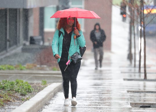 Alexis Ross of Milwaukee walks in the rain down North 6th Street on Sunday. Ross was on her way to the bus stop before heading to work at Walmart in Franklin.