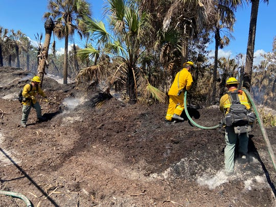 Firefighters work to mop up containment lines along the 36th Avenue SE fire in Golden Gate Estates on Sunday.