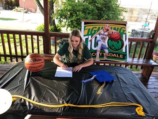 Bloomfield's Halle Payne signs her National Letter of Intent at her home on Saturday to continue her basketball career at Scottsdale Community College.