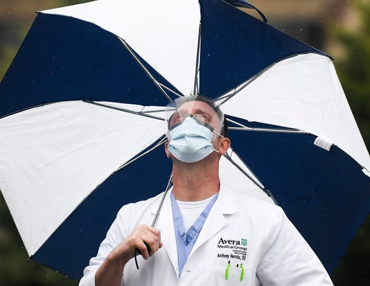 Dr. Anthony Hericks watches as South Dakota Air National Guard's 114th Fighter Wing flies over to honor healthcare workers during the coronavirus pandemic on Saturday, May 16, 2020 at Avera in Sioux Falls, S.D.