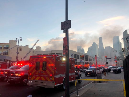 Firefighters and other first responders work the perimeter of an explosion in downtown Los Angeles that has injured multiple firefighters and caused a fire that spread to several buildings on Saturday.
