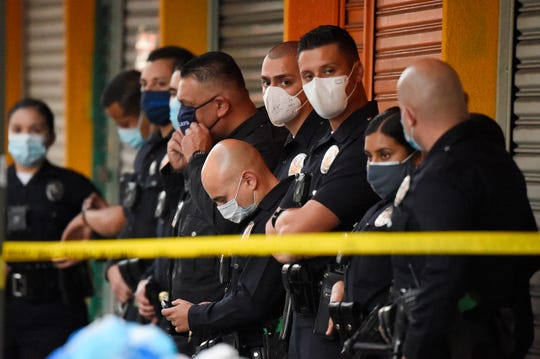 Los Angeles Police Department officers stand at the scene of a structure fire that injured multiple firefighters, according to a fire department spokesman, Saturday, May 16, 2020, in Los Angeles. (AP Photo/Mark J. Terrill)