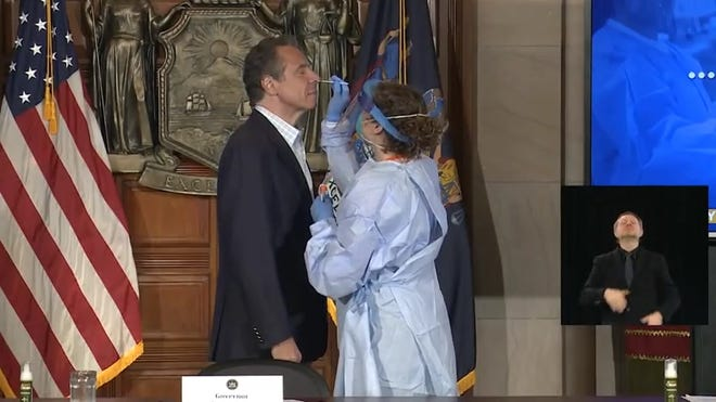 New York Gov. Andrew Cuomo submits to a nasal swab for a COVID-19 test during his daily coronavirus briefing on May 17, 2020.
