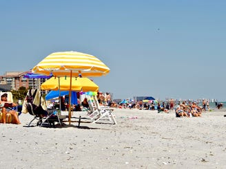 Visitors sit on the sand on Myrtle Beach, S.C., on Saturday, May 2, 2020. Visitors are allowed to return, as stay at 真人百家家乐官网网站home orders have lifted in the area. Statuses of restrictions vary around the state of South Carolina.