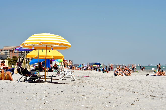 Visitors sit on the sand on Myrtle Beach, S.C., on Saturday, May 2, 2020. Visitors are allowed to return, as stay at home orders have lifted in the area. Statuses of restrictions vary around the state of South Carolina.