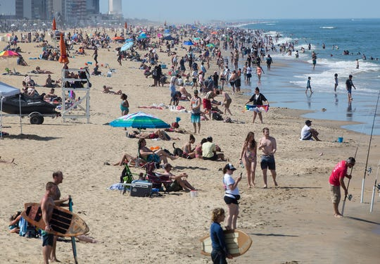Warm weather pulls crowds to the coast, Saturday May 16, 2020 in Virginia Beach, Va.