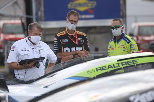 A NASCAR official with a mask inspect cars prior to the NASCAR Cup Series The Real Heroes 400 at Darlington Raceway on May 17, 2020 in Darlington, South Carolina. NASCAR resumes the season after the nationwide lockdown due to the ongoing Coronavirus (COVID-19).