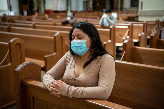 Monica Asitimbay prays at Holy Trinity Church in Hackensack, New Jersey, on Sunday, May 17, 2020, the first the day the church reopened during the coronavirus pandemic.