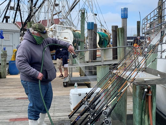 A fisherman with a face covering washes down fishing rods following a fishing trip aboard the Dauntless party boat on May 17, 2020.