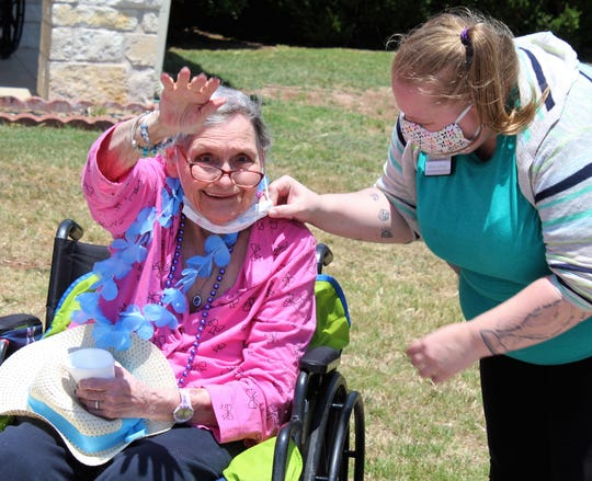 A resident of Willow Springs Health & Rehabilitation Center has her face mask adjusted by a staff member while waving to the Honk Your Horn parade passing by the South Seventh Street facility May 18.