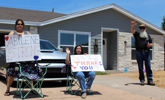 From left, April Chevrie, Alicia Holland and Granddad, aka Bob Mantooth, wave to participants in the Honk Your Horn parade through neighborhoods damaged and rebuilt after the 2019 tornado in west-central Abilene. The parade was one year to the day of the EF-2 tornado.