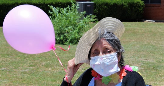 A gust of wind almost takes the straw hat of a resident of Willow Springs Health & Rehabilitation Center while she watches the May 18 Honk Your Horn parade pass by.