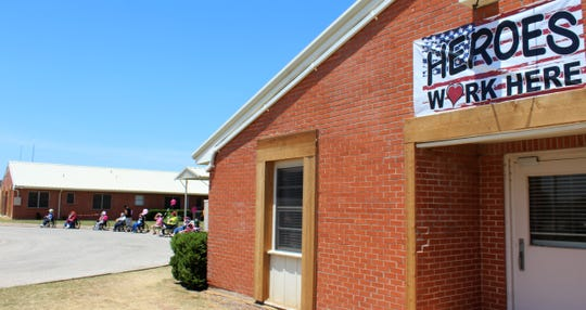 A banner honoring employees of Willow Springs Health & Rehabilitation Center is displayed for passersby on South Seventh Street. On Monday, some of the residents were taken outside to watch the Honk Your Horn parade go by, each given a balloon to celebrate surviving a tornado that damaged the facility (see the new wood frames) one year earlier.