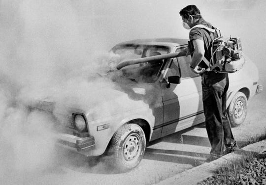 FILE - In this 1980 file photo, a worker at an auto dealership in Moscow, Idaho, uses a blower to remove ash from the eruption of Mount St. Helens  from a car in Washington state, more than 350 miles away. May 18, 2020, will mark the 40th anniversary of the eruption of the volcano. (Moscow-Pullman Daily News via AP, File)