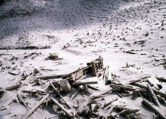 FILE - In this May 20, 1980, file photo, a wrecked logging truck and crawler tractor are shown amidst ash and downed trees near Mount St. Helens two days after the volcano erupted in Washington State. May 18, 2020, is the 40th anniversary of the eruption. (AP Photo/File)