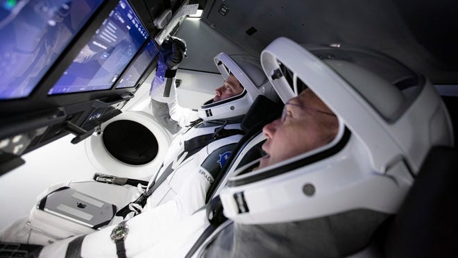 NASA astronauts Bob Behnken and Doug Hurley participate in a SpaceX Crew Dragon flight simulator in this March 2020 photo.