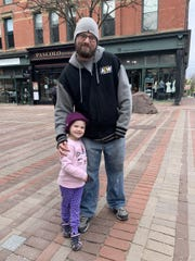 Chris Feerick and his daughter walk on Church Street for some fresh air the day retail businesses reopened in Vermont. May 18, 2020.