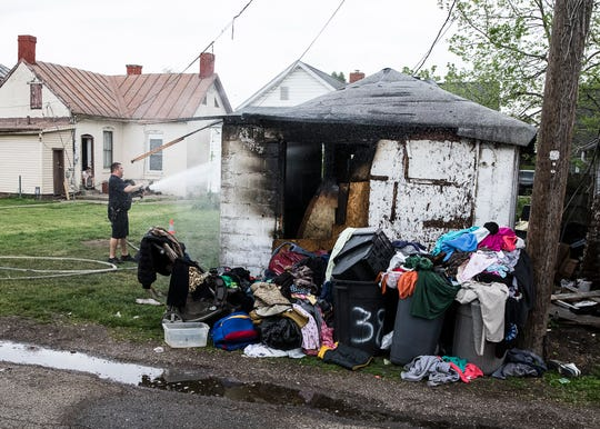 A member of the Chillicothe Police sprays water on the burnt-out garage after a structure fire on the 300 block of McKellar Street, May 2020.