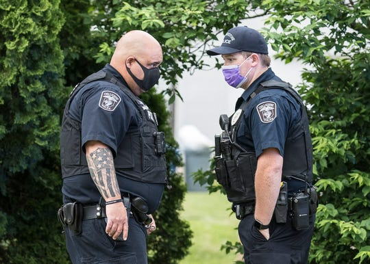 Police discuss the scene at a house fire on McKeller Street, May 2020