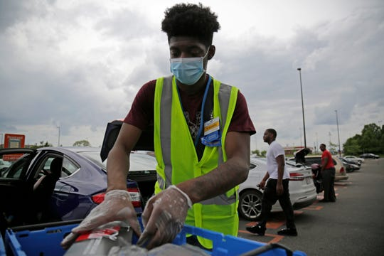 Personal shopper Kamari Barrow loads a customer's order into their car in the curbside pickup section of the parking lot at the Walmart Super Center in the Westwood neighborhood of Cincinnati on  Sunday, May 17, 2020.