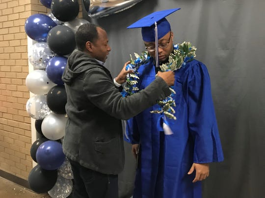 During the filming of the Fort Campbell High School 2020 graduation ceremony on May 6, Sgt. 1st Class Willie Williams places a money lei on his son, Kamari, graduating senior.