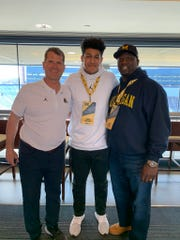 Southeast Polk 2023 offensive lineman Kadyn Proctor (middle) poses with Michigan head coach Jim Harbaugh (left) and his father during a visit to Michigan.