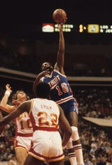 Detroit Pistons center Bob Lanier goes up against Atlanta Hawks forwards John Drew (22) and Steve Hawes (10).