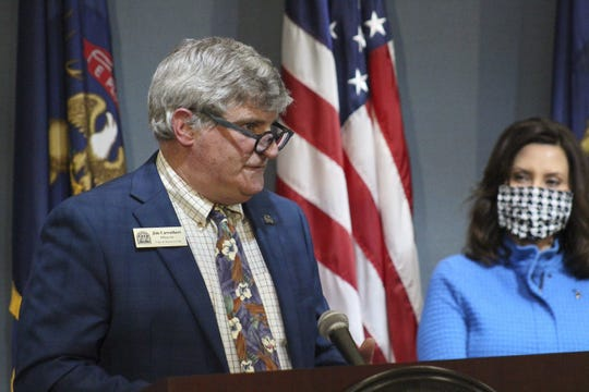 Traverse City Mayor Jim Carruthers speaks as Governor Gretchen Whitmer looks on during an update on COVID-19 at a press conference on April 24, 2020.