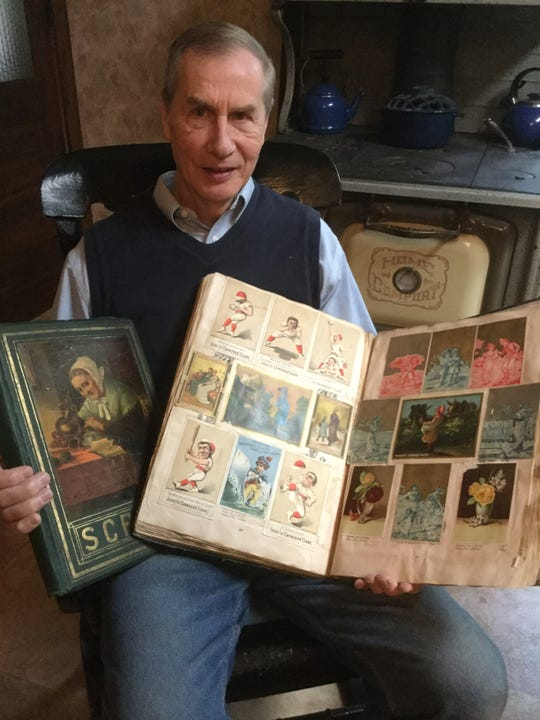 John Kemler of Alma holds scrapbooks he's put together for his collection of Victorian trade cards.