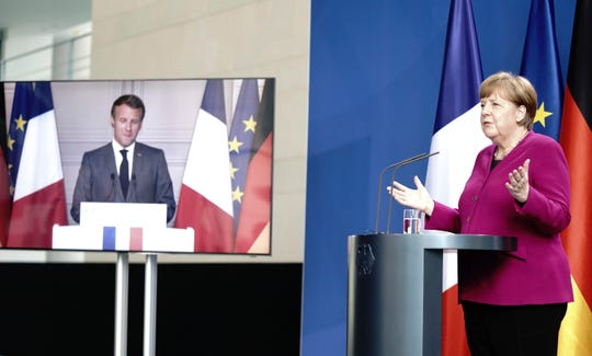 German Chancellor Angela Merkel talks to French President Emmanuel Macron, connected by video, during a press conference after a joint video conference in Berlin, Germany, Monday, May 18, 2020.