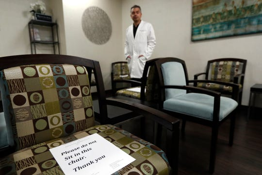 Dermatologist Dr. Seemal Desai poses for a photo in the waiting room of his office in Plano, Texas, Thursday, May 7, 2020.