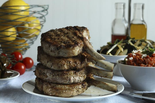 The pork chops are marinated with olive oil, lemon zest and juice, garlic, oregano, salt, pepper and thyme.