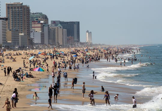 Warm weather draws crowds to the oceanfront, Saturday, May 16, 2020 in Virginia Beach, Virginia.