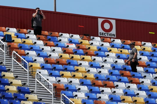 Officials monitor empty grandstands at Darlington Raceway Sunday before the start of the Real Heroes 400 NASCAR Cup Series auto race.