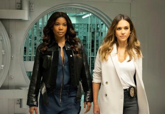 "Gabrielle Union, left, and Jessica Alba in a scene from ""L.A.'s Finest."" The series will premiere in the fall.  Union is among those awaiting guidance on how actors and crews can safely return to work. The police drama combines shoot-'em-up action with more intimate scenes, both a test of how social distancing and story demands will co-exist."