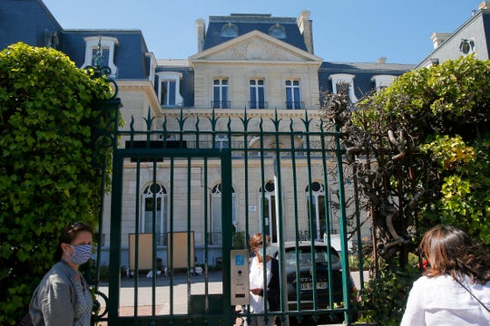 A woman wearing a face mask stands behind the closed Jeanne d'Arc private school in Roubaix, northern France, Monday.