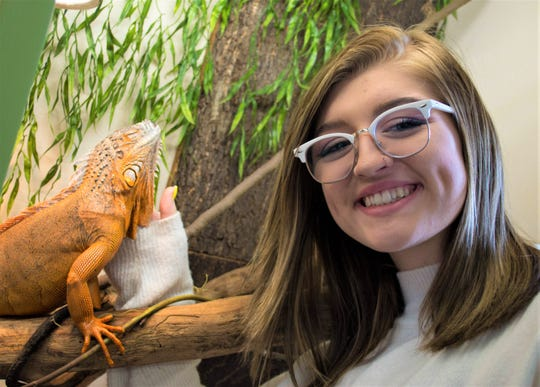 Kailey Cornell pets Frankie the red iguana at Wet Pets-N-Pals in Port Clinton. Kailey's father, Dave Cornell, opened the shop, which sells fish and reptiles, in spring 2019.