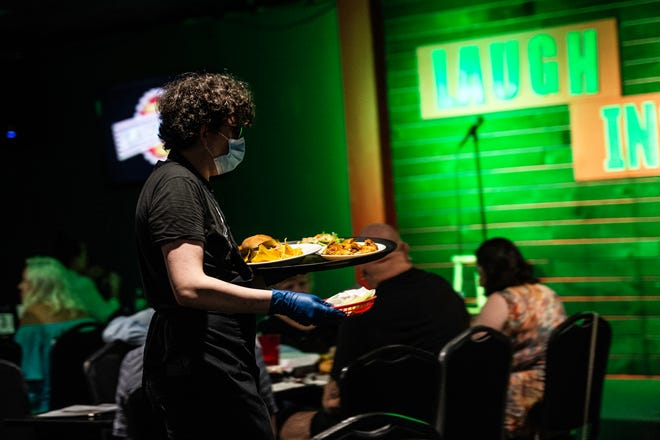 A server delivers food to a table during a comedy event at the Laugh In Comedy Cafe in Fort Myers, Fla., on Friday, May 15, 2020. The cafe removed seating to allow for social distancing, and servers are wearing masks and gloves.
