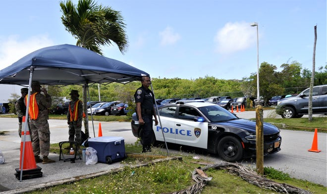 Guam police and military members monitor the parking lot of the Department of Revenue and Taxation, Barrigada, Guam, May 18, 2020