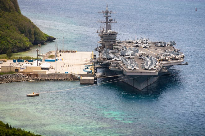 The aircraft carrier USS Theodore Roosevelt is moored pier side at Naval Base Guam Friday. After Theodore Roosevelt's COVID-negative crew began returning from from quarantine and making preparations to return to sea, 13 sailors who had recovered from the virus fell ill and re-tested positive.